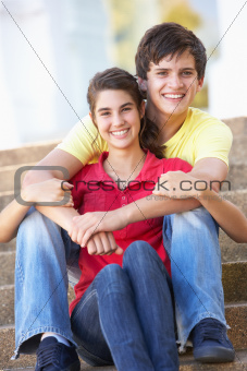 Teenage Couple Sitting On College Steps Outside
