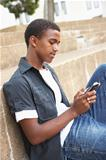 Unhappy Male Teenage Student Sitting Outside On College Steps Using Mobile Phone