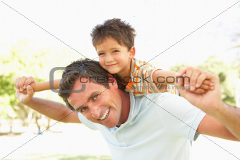 Father Giving Son Ride On Back In Park
