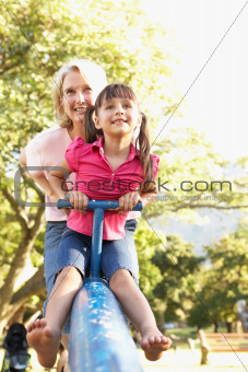 Grandmother And Granddaughter Riding On See Saw In Playground