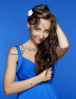 beautiful woman with brown hair and blue eyes isolated on blue