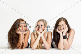 three young female friends lying on the floor, looking ar camera, smiling