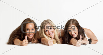 three young female friends lying on the floor showing thumbs up