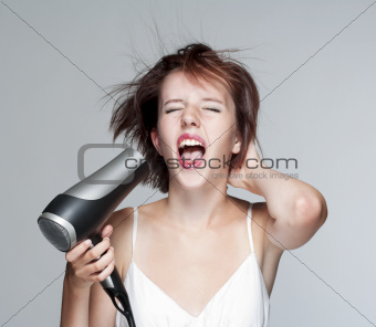 beautiful teenage girl blowing her hair with hairdryer, screaming - isolated on gray