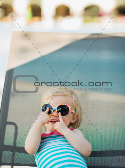 Baby in glasses laying on sun bed