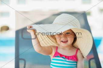 Baby in beach hat sitting on sun bed