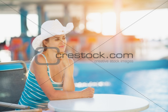 Portrait of dreaming woman at pool bar looking on copy space