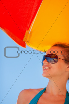 Happy woman in sunglasses on beach looking on copy space