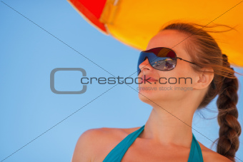 Happy woman in sunglasses on windy beach looking on copy space