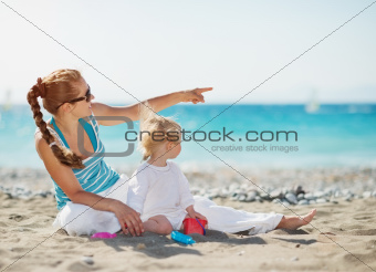 Mother pointing baby on copy space