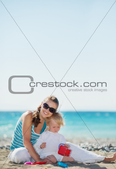 Happy mother and baby playing on beach