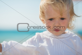 Portrait of thoughtful baby on beach