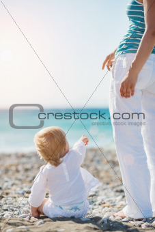 Baby showing mother something on beach. Rear view