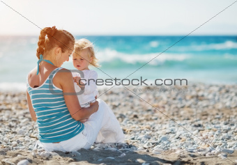 Mother spending time with baby on beach