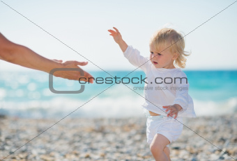 Baby walking to mothers outstretched hands
