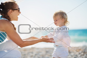 Mother and baby holding hands on beach