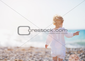 Baby walking on beach. Rear view