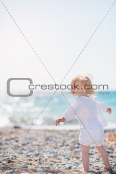 Baby walking on beach and looking on copy space