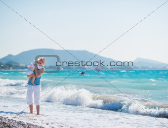 Baby hugging mother standing at sea shore