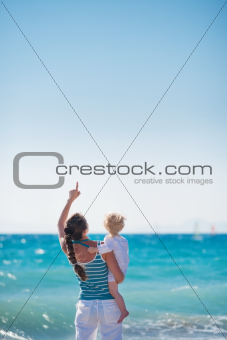 Mother and baby at sea shore pointing up on copy space