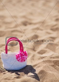 Closeup on child handbag on beach sand