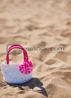Closeup on child handbag on beach sand