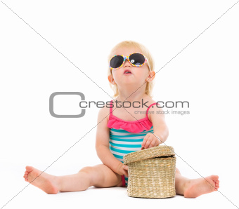 Baby in swimsuit and sunglasses looking up