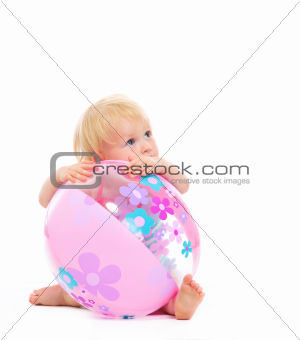 Baby behind beach ball looking on copy space
