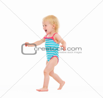 Happy baby in swimsuit running on white