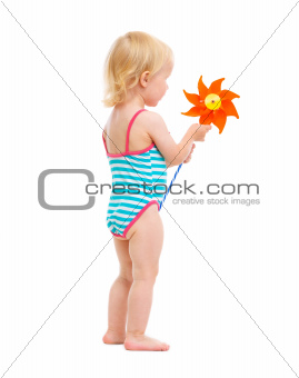 Baby girl in swimsuit holding pinwheel