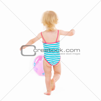 Baby girl in swimsuit playing with ball. Rear view