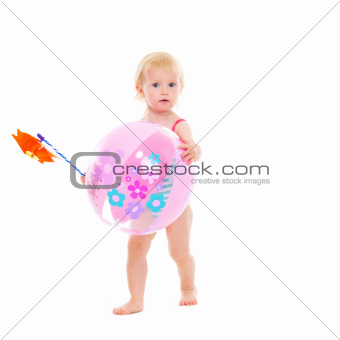Baby girl in swimsuit holding pinwheel and beach ball