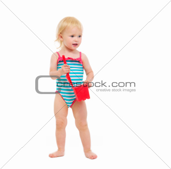 Baby girl in swimsuit holding bucket and shovel looking in corner