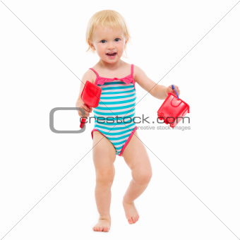 Baby girl in swimsuit holding bucket and shovel
