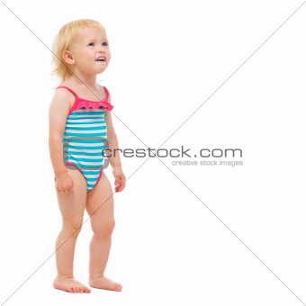 Baby girl in swimsuit looking on copy space