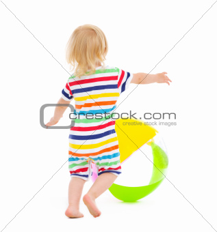 Baby in swimsuit playing with ball. Rear view