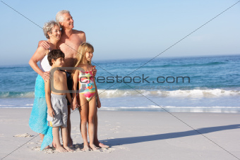 Grandparents And Grandchildren Standing On Sandy Beach