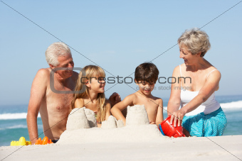 Grandparents And Grandchildren Building Sandcastles Together On Beach Holiday