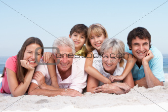 Three Generation Family Relaxing On Beach Holiday