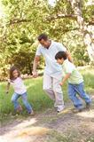 Father And Children Enjoying Walk In Park