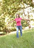 Young Woman Running Through Long Grass In Park