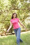 Young Woman Walking Through Long Grass In Park