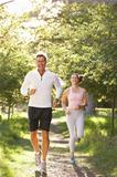 Middle Aged Couple Jogging In Park