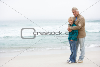 Grandfather And Son Standing On Winter Beach Together