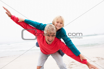 Grandfather Giving Grandson Piggy Back On Winter Beach