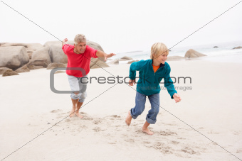 Grandfather Chasing Grandson Along Winter Beach