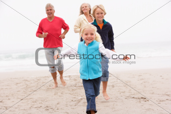 Grandparents And Grandchildren Running On Winter Beach Together