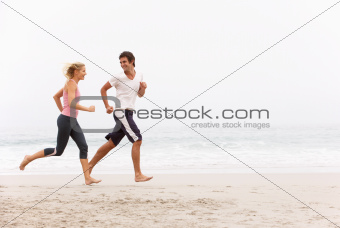 Young Couple Running Along Winter Beach