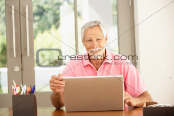 Senior Man Using Laptop At Home