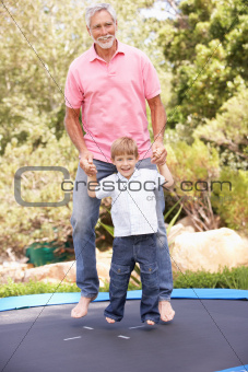 Grandfather And Grandson Jumping On Trampoline In Garden